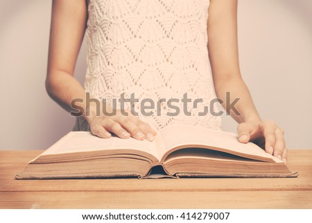 Vintage tone of A close-up of a christian woman reading the bible. - stock photo