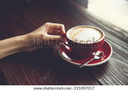 Vintage tone of Female hands holding cup of coffee on wooden table. - stock photo