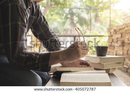 Vintage tone of man reading book in library .Retro filter effect,soft focus,low light.(selective focus)  - stock photo
