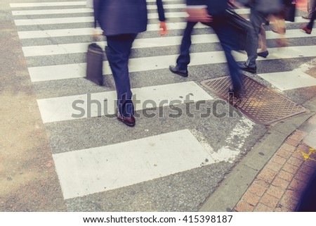 vintage tone of Motion blurred pedestrians crossing street - stock photo