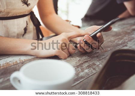 Vintage tone of people using smart phones in cafe. - stock photo