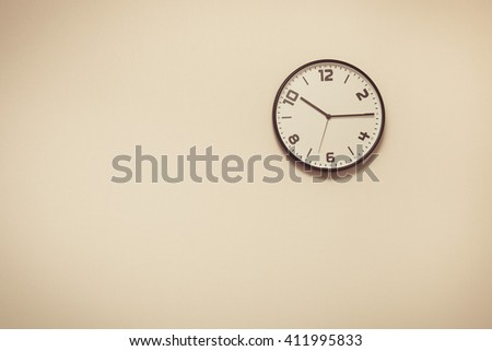 Vintage tone of Round metal clock on white wall - stock photo