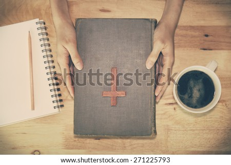 Vintage tone of wooden Christian cross on the Bible during prayer. - stock photo