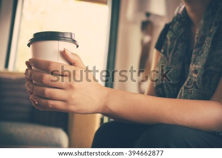 Vintage tone of Young woman drinking coffee from disposable cup - stock photo