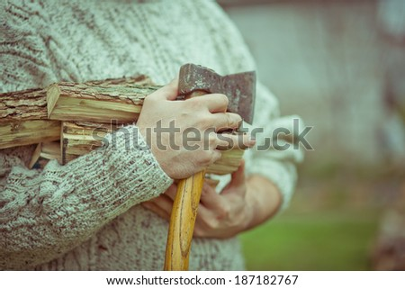 Vintage toned image of a man with axe and bunch of wooden logs for picnic. focus on hand - stock photo