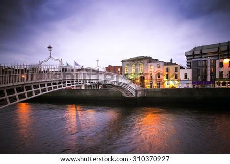 Vintage toned image of historic Ha'penny Bridge over the River Liffey in Dublin Ireland - stock photo