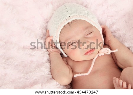 Vintage toned Newborn baby girl wearing a knitted bonnet. - stock photo