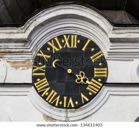 Vintage tower clock with roman numerals on white church wall in old part of Tallinn, Estonia - stock photo