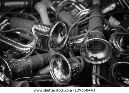Vintage toy trumpets at flea market. Black and white. - stock photo