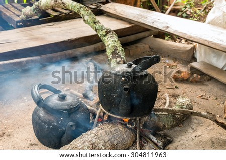 Vintage traditional kettle for boiling water on Wood sticks - stock photo
