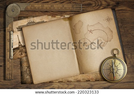 Vintage treasure map in open book with compass and old ruler. Adventure and travel concept. - stock photo