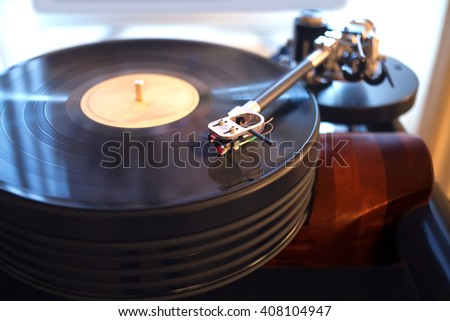 Vintage turntable rotating LP record in a room with subdued light. Horizontal view closeup - stock photo