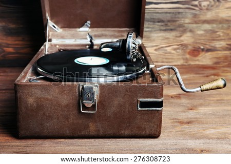 Vintage turntable vinyl record player on wooden background - stock photo