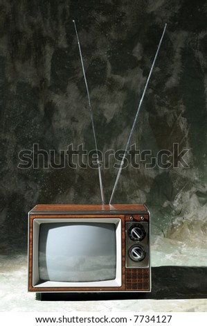 Vintage TV with knobs and antenna over a textured background - stock photo