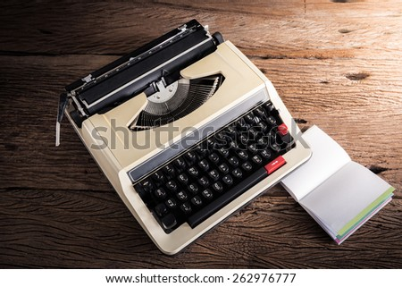 Vintage typewriter and a blank notebook and pen, retro colors - stock photo