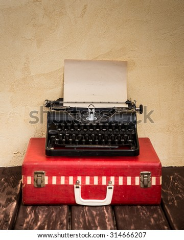 Vintage typewriter and classic red suitcase. Travel concept - stock photo