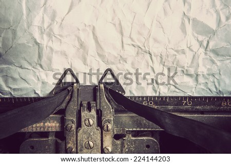 Vintage typewriter and crumpled paper. Focus on ribbon.  - stock photo