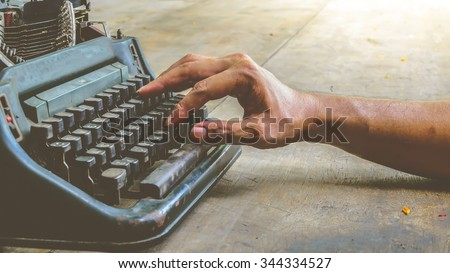 Vintage typewriter and human hand on a wood table , process in vintage style - stock photo