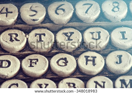 Vintage typewriter detail with stone carved keys photographed with shallow depth of field. Selective focus image cross processed for vintage look - stock photo
