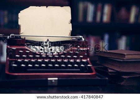 Vintage typewriter in a library with barrister bookcases from 1920s era with vintage filtered effect - stock photo