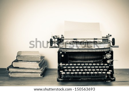 Vintage typewriter, old books on table sepia photo - stock photo