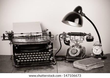 Vintage typewriter, old telephone, desk lamp, book, clock - stock photo