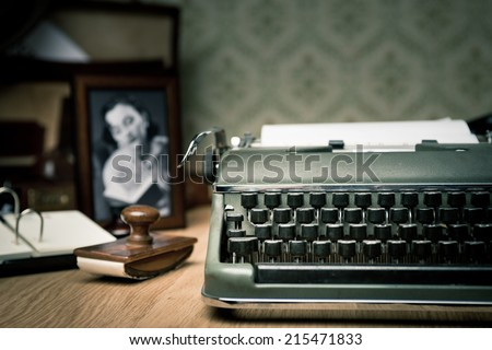 Vintage typewriter on a wooden desk with old frame and picture on background. - stock photo