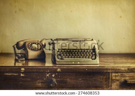 Vintage typewriter, telephone,on table desaturated photo - stock photo