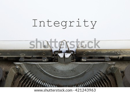 """vintage typing machine and white blank paper with words """"integrity"""" - stock photo"""