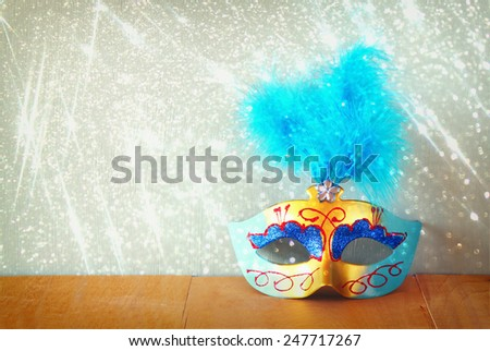 vintage Venetian masquerade mask on wooden table with glitter overlay - stock photo