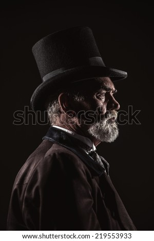Vintage victorian man with black hat and gray hair and beard. Studio shot against dark background. - stock photo
