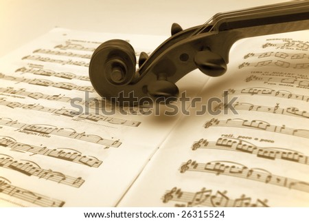 Vintage violin neck resting on a sheet music - stock photo