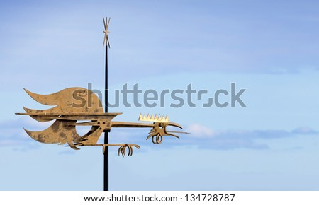 Vintage weather vane cock bird on the red roof above blue sky. Old part of Tallinn, Estonia - stock photo