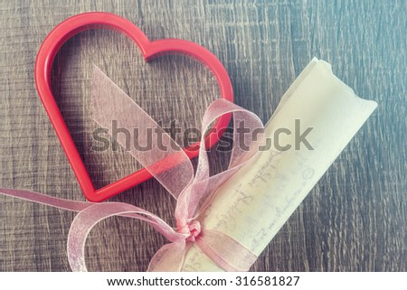 Vintage wedding invitation with pink ribbon and a red heart. Cross processed image with selective focus - stock photo