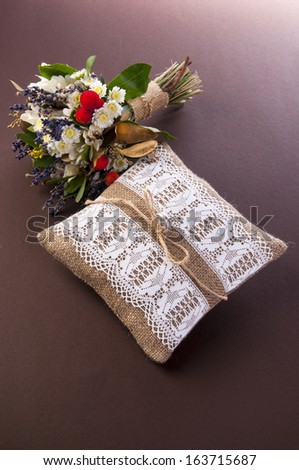 Vintage wedding pillow with ring and field flowers bouquet on pink background - stock photo