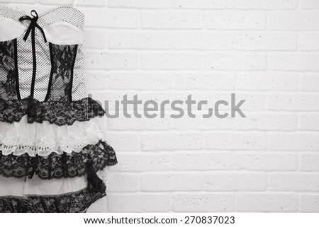 Vintage white dress on a brick wall background - stock photo