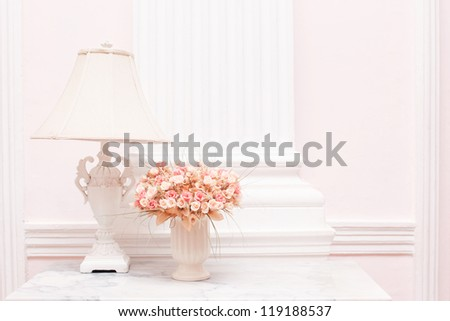 Vintage white lamp and flower vase on white desk against white background - stock photo