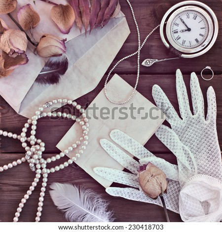 Vintage women's jewelry and gloves. Retro concept with dried roses on a wooden background - stock photo