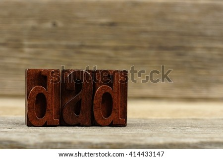 Vintage wood letters spelling DAD on a rustic wooden background - stock photo