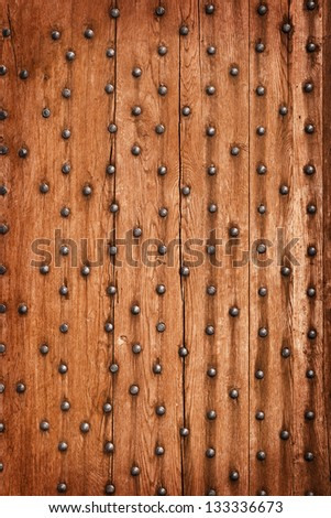 Vintage wooden background with metal rivets. The gate of the old castle. - stock photo
