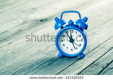 Vintage wooden background with retro alarm clock - stock photo