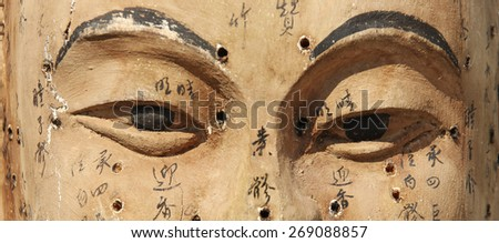 Vintage wooden Buddha face with indicated acupuncture points and names (manual focus on eyes) - stock photo