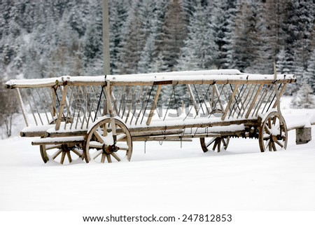 vintage wooden carriage under snow in forest - stock photo