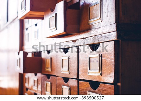 Vintage wooden catalog with some drawers opened. One of the drawers has label with the word Data on it. - stock photo