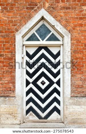 Vintage wooden door and old brick wall. Vintage exterior details - stock photo