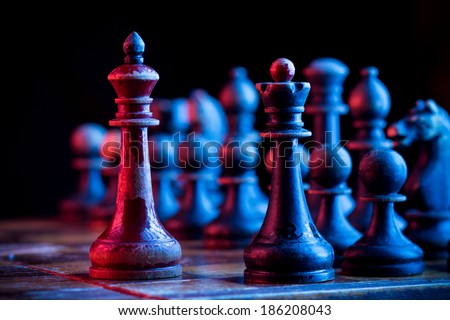 Vintage wooden king and queen chess piece in front of black chess set. - stock photo