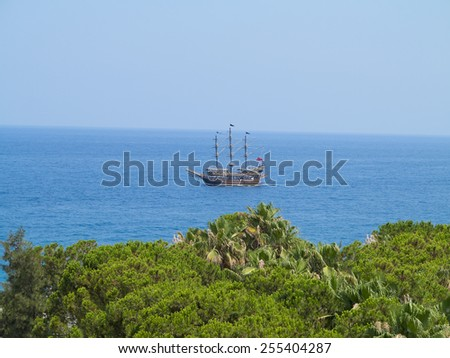 Vintage wooden pirate old ship in blue sea - stock photo