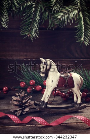 vintage wooden rocking horse toy on christmas background in retro style - stock photo