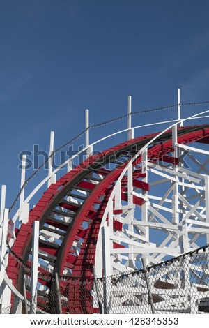 Vintage wooden roller coaster with red track and white wood frame against a clear blue sky.  This is the iconic Big Dipper roller coaster at the Boardwalk amusement park in Santa Cruz, California.  - stock photo