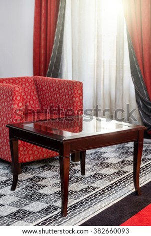 Vintage wooden table in the interior with red armchair - stock photo